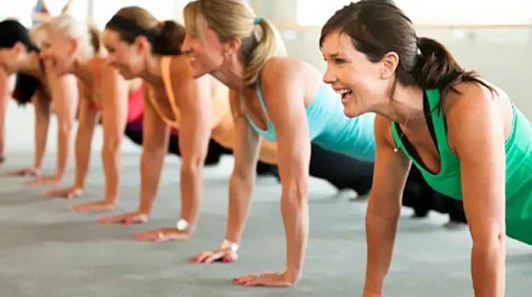 физическая активность, занятия спортом это весело, девушки стоят в планке на тренировке в зале