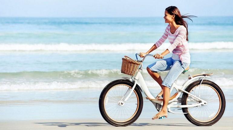 девушка едет на велосипеде, велопрогулка на берегу моря