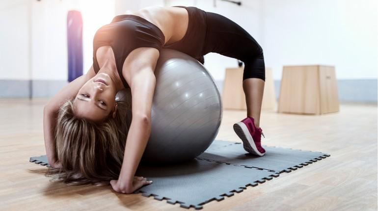 занятие на фитболе, девушка делает упражнения на растяжку