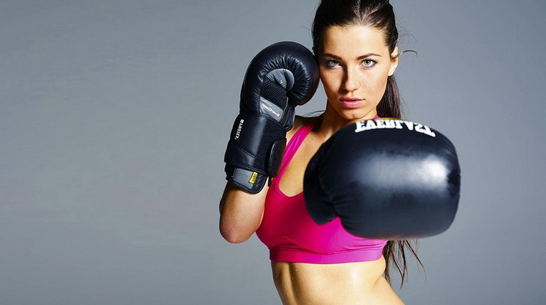 девушка занимается боксом, тренировка в боксерских перчатках