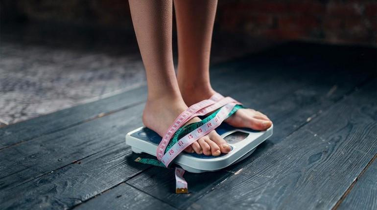 ноги девушки стоят на весах обмотаны сантиметровой лентой, мотивация к снижению веса