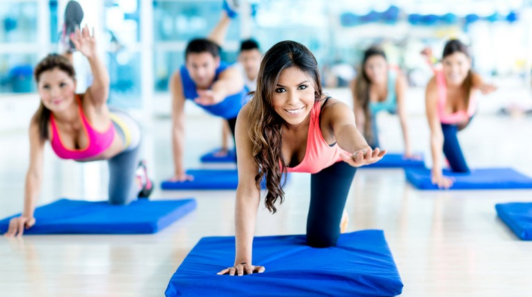 девушка на групповой тренировке в спортклубе, занятия на спортивном коврике