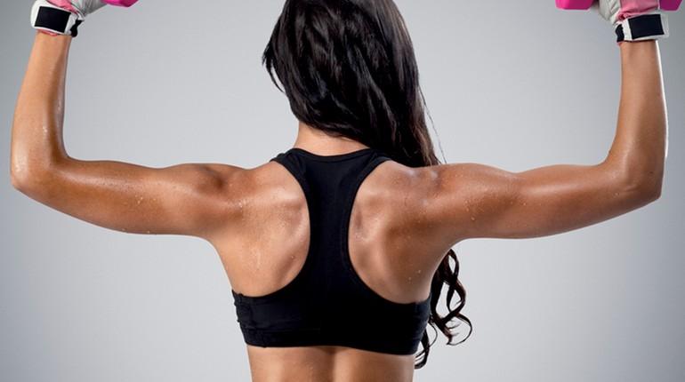 спина натренированной девушки, девушка с гантелями, тренировка на верхние группы мышц