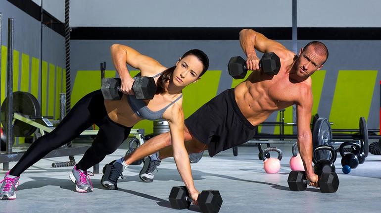 девушка и парень на тренировке, занятия с гантелями, тренировка в зале