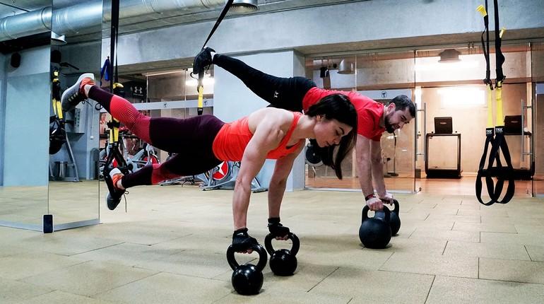 фитнес-пресс, занятия в спортзале, девушка и парень на тренировке