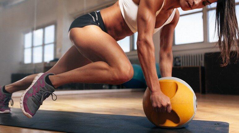 тренировка в спортзале, упражения для укрепления мышц пресса и корпуса, девушка лелает упражнения со спортивным оборудованием