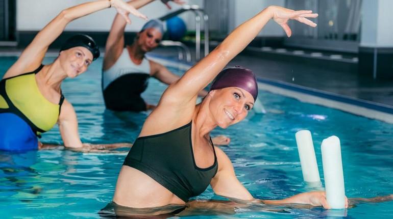 занятия аквааэробикой, групповые занятия в бассейне, девушка в купальнике и резиновой шапочке занимается в бассейне