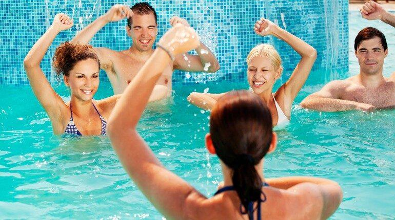 групповые упражнения в бассейне, девушки и парень занимаются аквааэробикой