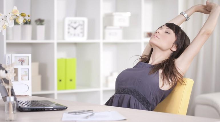 девушка устала сидеть за компьютером, девушка работает в офисе, девушка потягивается за рабочим столом