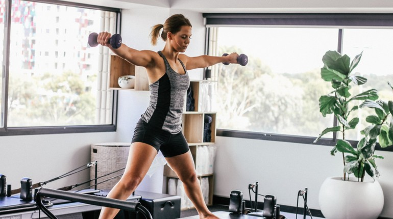 девушка тренируется с гантелями и на тренажере, интенсивные тренировки