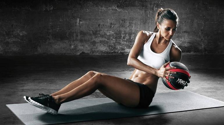 девушка делает скручивания с медболом, девушка занимается в спортзале с мячом