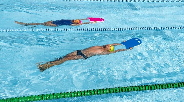 плаванье на спине, упражнения в бассейне, заплыв на спине с доской