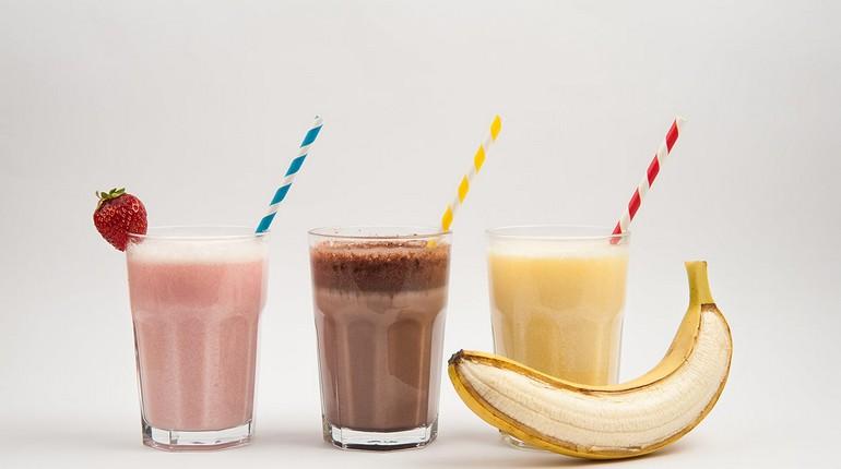 спортивные коктели вкусные и питательные, клубничный банановый и шоколадный коктель, три стакана с коктелями разных вкусов