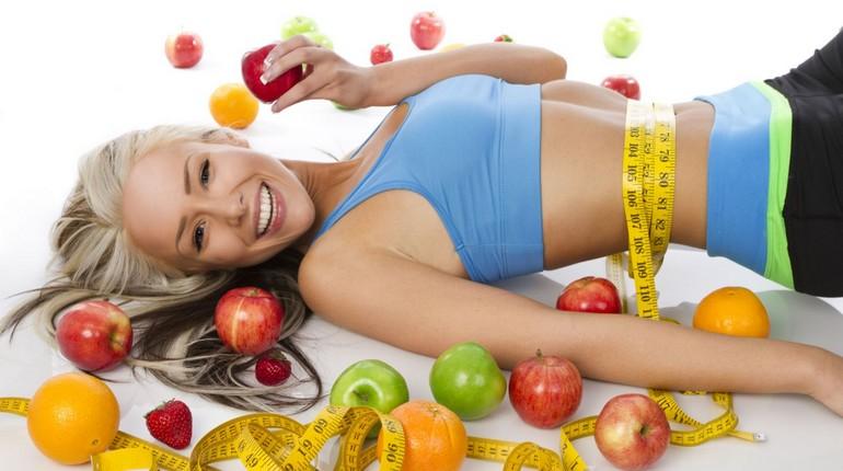 девушка позирует с фруктами и сантиметровой лентой на талии, спортивное питание