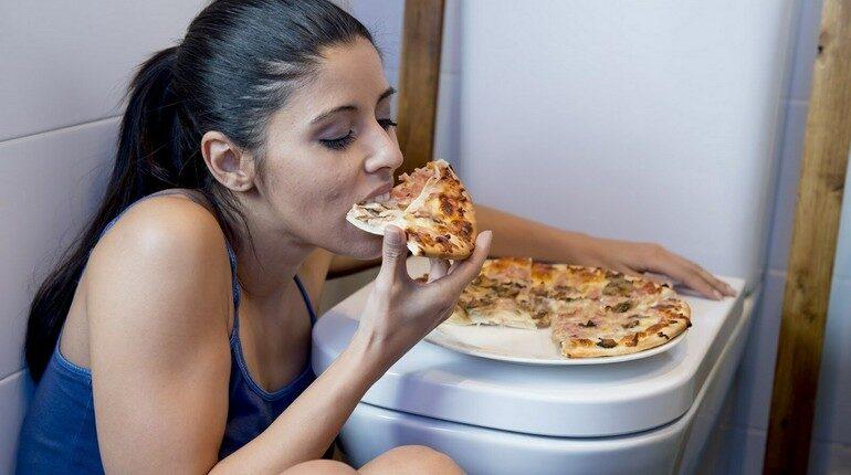 девушка поедает пицу в туалете, девушка сидит на полу обхватив унитаз и ест пицу стоящую на крышке унитаза