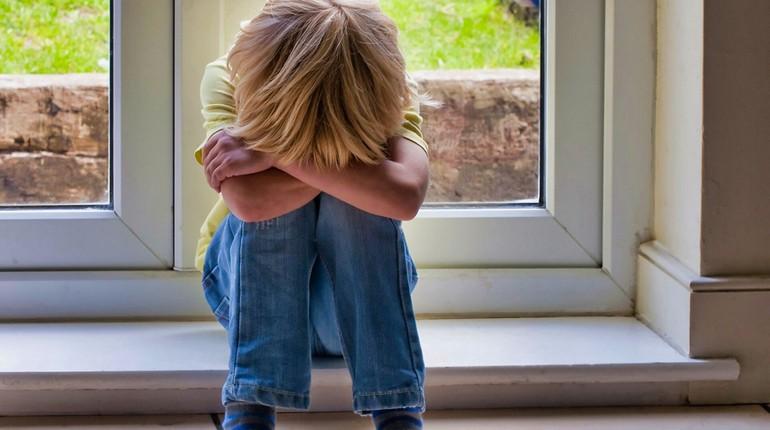 мальчик сидит на подоконнике и грустит, ребенок переживает, грустный ребенок