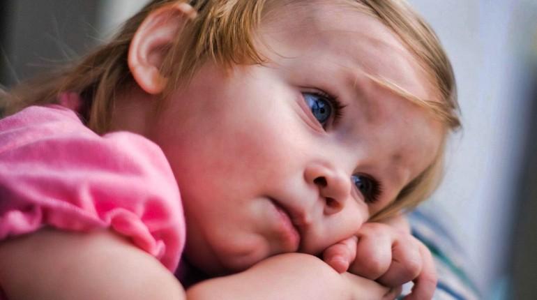 девочка грустит, унылый и грустный ребенок, девочка положила руки под щеку и задумалась